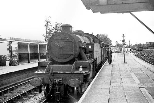A view looking west from the island platform at Menai Bridge in August 1964. The goods train is standing at the up Afon Wen line platform which was used by passenger services travelling towards Bangor. To the left can be seen the down Afon Wen line platform. The platform that can be seen to the right served trains travelling towards Holyhead. Photo by Bevan Price